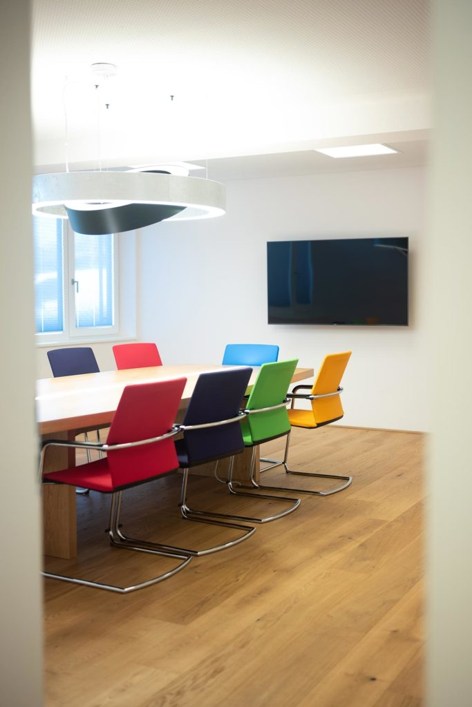 Büroneubau Codalonga in Bergheim, Besprechungstisch mit bunten Stühlen, Planungsleistungen Blaupause Immobilien